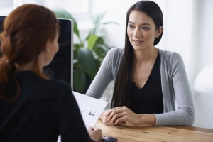 Young woman during a job interview. Recruiter with back to viewer